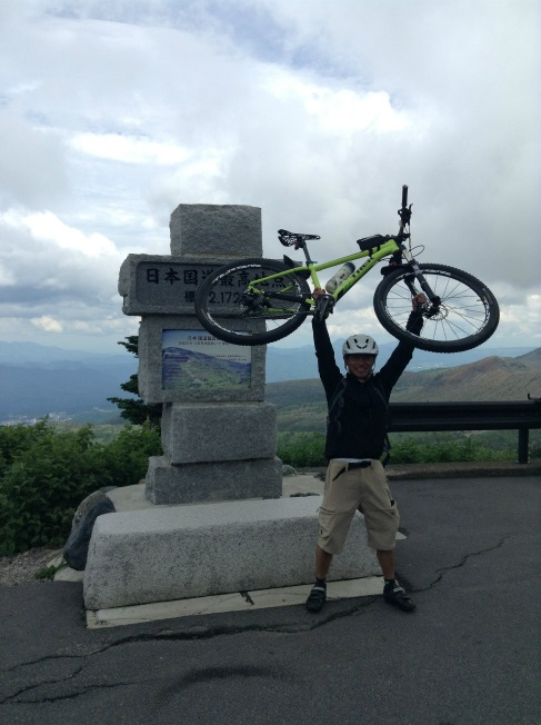 渋峠でマウンテンバイクを持ち上げる人